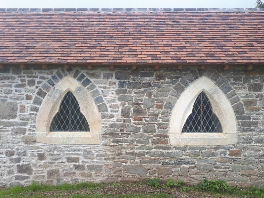 The restored east wall. The left side was rebuilt from below the ground. Part of the stone surround of the right window was renewed.
